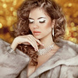 Luxury fashion beauty woman in fur coat over golden bokeh backgr — Stock Photo