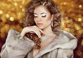 Luxury fashion beauty woman in fur coat over golden bokeh backgr — Stock Photo