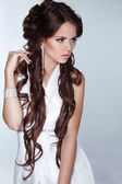 Beautiful woman with long brown hair wearing in white dress isol — Stock Photo