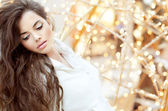 Sensual brunette girl with long wavy hair over bright lights bli — Stock Photo