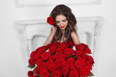 Schöne Brünette Frau mit Blumenstrauß viele rote Rosen — Stockfoto