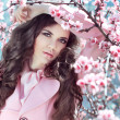Beautiful brunette girl posing over Pink Spring Cherry blossoms. — Stock Photo