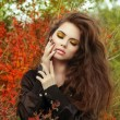 Beautiful young woman with long hair posing outdoors in autumn p — Stock Photo