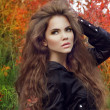 Beautiful brunette model woman posing with long wavy hair at col — Stock Photo