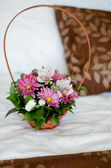 Beautiful bouquet of colorful flowers in basket against the bed  — Stock Photo
