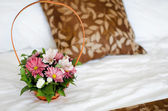 Beautiful bouquet of colorful flowers in basket against the bed  — Stock fotografie