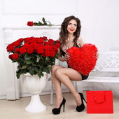 Beautiful Brunette Woman holding red heart over bouquet of roses — Stock Photo