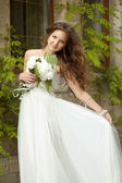 Beautiful happy bride with  long wavy hair and wedding makeup ho — Stock Photo