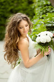 Beautiful young bride with  long wavy hair and wedding makeup ho — Stock Photo