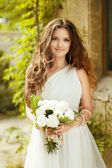 Beautiful young bride with wedding makeup and long wavy hair sty — Stock Photo