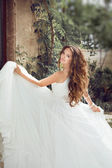 Beauty fashion bride girl gamboling with wedding blowing dress, — Stock Photo
