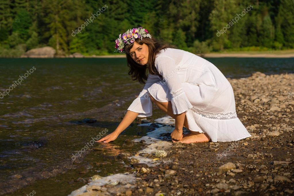 Mother Nature Kneeling at Shoreline  Stock Photo #13558289