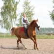 Beautiful young blonde woman riding chestnut horse — Stock Photo #14904811