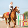 Beautiful young blonde woman riding chestnut horse — Stock Photo