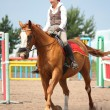 Beautiful young blonde woman riding chestnut horse — Stock Photo #14906823