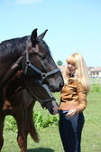 Blonde woman and black horse — Stock Photo