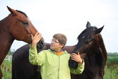 Teenager boy and horses from the herd — Stock Photo