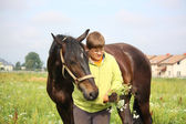 Smiling teenager boy with horses at the field — Stock Photo