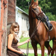 Portrait of teenage girl and chestnut horse near the wooden stab — Stockfoto