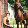 Portrait of teenage girl and chestnut horse near the wooden stab — Стоковая фотография