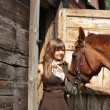 Portrait of teenage girl and chestnut horse near the wooden stab — Foto Stock