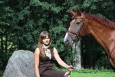 Beautiful teenage girl resting on the rock in park and horse sta — Stock Photo