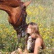 Girl sitting on the ground and chestnut horse standing near — Stock Photo