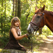 Beautiful girl and brown horse portrait in mysterious forest — Stockfoto