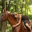 Stock Photo: Girl in dress and brown horse portrait in forest