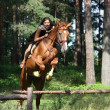 Teenager girl jumping over the fence with horse — Stock Photo