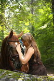 Beautiful girl and brown horse portrait in mysterious forest — Stock Photo