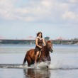 Beautiful teenage girl riding horse in the river — Stock Photo #27291303