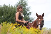 Beautiful teenager girl riding horse at the field of flowers — Stock Photo