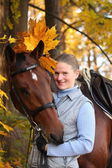 Beautiful blonde woman and brown horse — Stock Photo