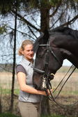 Young blonde woman and black horse smiling — Stock Photo