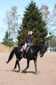 Blonde woman riding black horse — Stock Photo