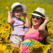 Beautiful woman and child with sunflower in spring field — Stock Photo #12142096