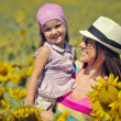 Beautiful woman and child with sunflower in spring field — Stock Photo #12143761