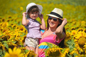 Beautiful woman and child with sunflower in spring field — Stock Photo