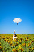Young woman with umbrella on field in sunflower — Stock Photo