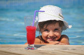 Little girl in the swimming pool with cocktail — Stock Photo