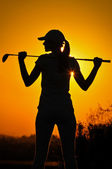 Girl playing golf on the sunset — Stock Photo