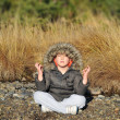 Boy meditating on the bank of mountain river — Stock Photo