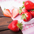 Strawberries on wooden plate — Stock Photo