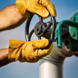 Stock Photo: Oil worker turning valve