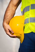 Man holding yellow helmet close up — Stock Photo