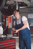 Car mechanic working in auto repair service — Stock Photo
