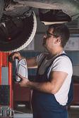 Car mechanic working in auto repair service — Stock Photo