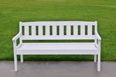 White bench on green grass — Stock Photo