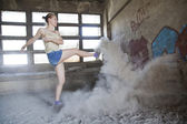 Woman jumping in dust — Stock Photo